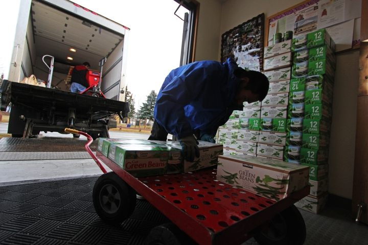 A Food Bank of Alaska worker picks up a donation of canned goods at Leake Temple AME Zion Church.