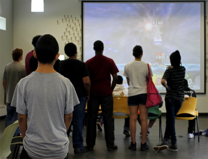 Teen volunteers and fans watch a video game tournament at the Mountain View Library July 29.