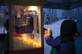 A neighborhood volunteer serves popcorn at the Mountain View Winter Festival at Mountain View Elementary School.